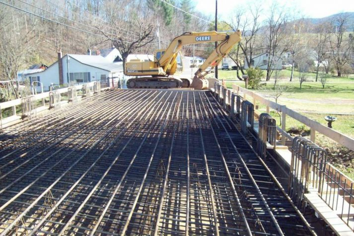 Construction company setting up the metal bars and latticing prior to pouring and setting the bridge