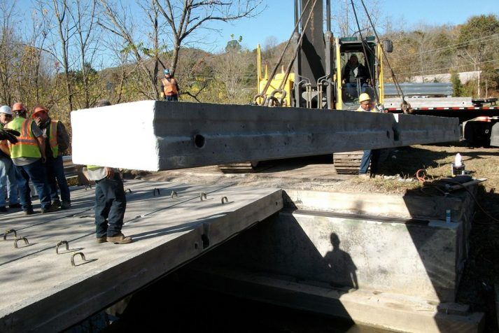 Construction company placing the concrete beams for the road across the bridge