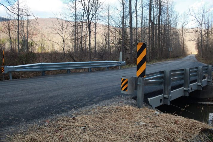 Completed bridge with signs over a creek completed by Estes Brothers Construction Company