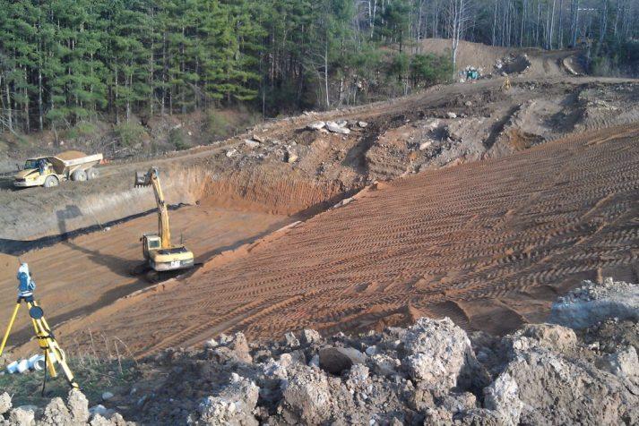 Construction company using heavy machinery to refine the surface on the backside of Bear Creek Dam