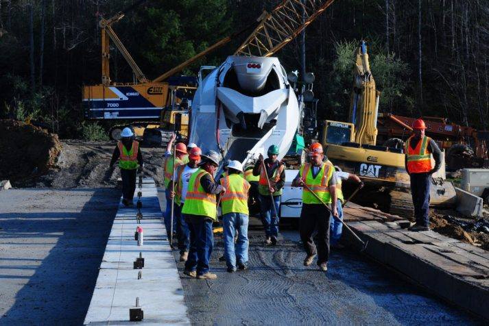 Construction workers pouring concrete at their Bear Creek Dam construction site project