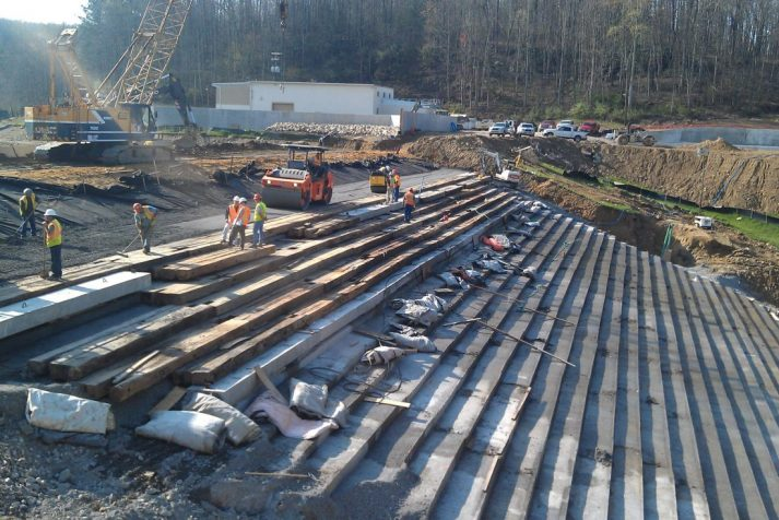 Construction workers preparing to complete the stepping on the backside of the Bear Creek Dam