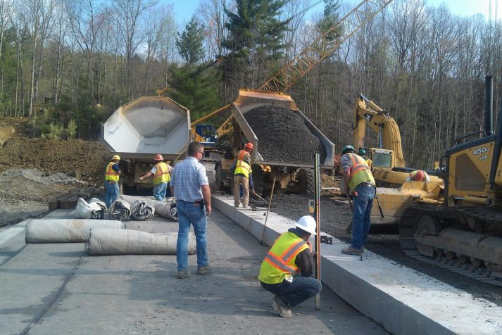 Dump truck pouring gravel as other construction workers evenly distribute on top of Bear Creek Dam