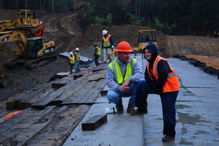 Construction worker talking with a child while others are working in the background at Bear Creek