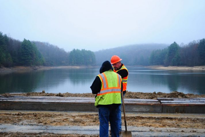 Pair of construction workers observing what is yet to be completed at the Bear Creek Dam