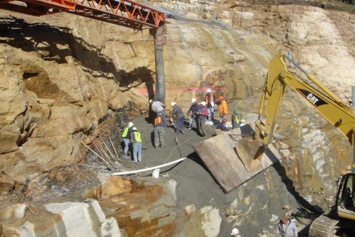 Construction workers pouring concrete on the side of a mountain for the dam (Big Cherry Project)